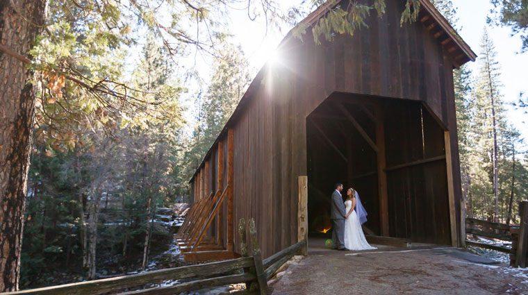 Yosemite wedding couple at the covered bridge in Wawona